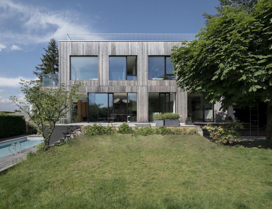 Projet de construction d'une maison familiale en bois sur une parcelle en pente et arborée en zone villa.